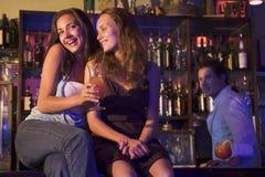 Deux jeunes femmes s'asseyant sur un compteur de bar image libre de droits