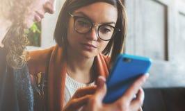 Deux jeunes femmes s'asseyent dans un café à la table et utilisent un smartphone La fille montre à son ami une photo sur l'écran  Images libres de droits