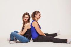 Deux jeunes femmes s'asseyent de nouveau au dos photo stock