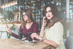Deux jeunes femmes s'asseyent en café à la table et au café potable Image libre de droits