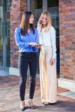 Deux jeunes femmes se tenant dehors avec le comprimé Photos stock