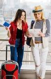 Deux jeunes femmes se tiennent avec une valise à la gare ferroviaire ou à l'aéroport Regardez la carte et le passeport Photos stock