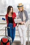 Deux jeunes femmes se tiennent avec une valise à la gare ferroviaire ou à l'aéroport Regardez la carte et le passeport Image libre de droits