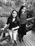 deux jeunes femmes se tiennent posantes sur le pont d'un jardin botanique Image libre de droits
