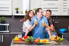 Deux jeunes femmes sont alimentées l'homme d'âge de midle de bananes Image libre de droits
