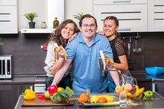Deux jeunes femmes sont alimentées l'homme d'âge de midle de bananes Photo libre de droits