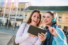 Deux jeunes femmes souriant, parlant et regardant sur le comprimé numérique Photographie stock