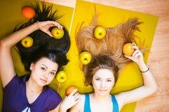 Deux jeunes femmes sportives de physique dans le gymnase se trouvent sur le plancher sur des tapis de yoga photographie stock