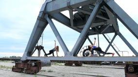Deux jeunes, femmes sportives, exécutent des exercices de force Ils se tiennent sur le faisceau en métal d'une grue de fret forme banque de vidéos