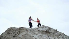 Deux jeunes, femmes sportives faisant des exercices dehors, sur le dessus arénacé de la carrière Sur la plage, port de cargaison, banque de vidéos
