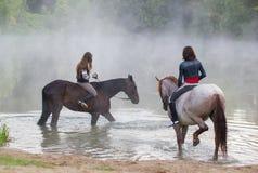 Deux jeunes femmes sur des chevaux entre dans le lac photos libres de droits