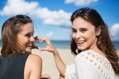Deux jeunes femmes sur la plage faisant le coeur signer rire Image stock