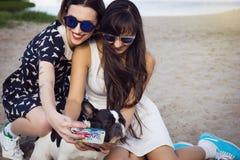 Deux jeunes femmes sur la plage prenant la photo avec le bouledogue français Image libre de droits