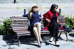 Deux jeunes femmes sur prendre un bain de soleil de banc Photos stock