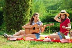 Deux jeunes femmes sur un pique-nique jouant une guitare et ayant l'amusement Image stock
