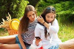 Deux jeunes femmes sur un pique-nique regardant l'écran de smartphone Image libre de droits