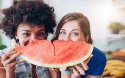 Deux jeunes femmes tenant la tranche de pastèque Images stock