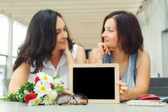 Deux jeunes femmes tenant le tableau noir vide avec le cadre en bois dans le Ca Photos stock