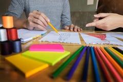 deux jeunes femmes travaillant comme couturiers et sketche de dessin Photos libres de droits