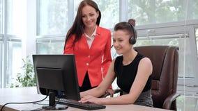 Deux jeunes femmes travaillent dans un bureau lumineux à l'ordinateur Discutez les déroulements des opérations et appréciez une a clips vidéos