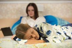 Deux jeunes femmes utilisant des pyjamas dans le lit Photographie stock libre de droits