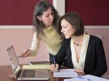 Deux jeunes femmes vivement habill?es compl?tant des formes ? un bureau de cru devant un ordinateur portable images libres de droits