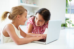 Deux jeunes filles à l'aide de l'ordinateur portable à la maison Images stock