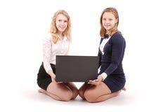 Deux jeunes filles à l'aide de l'ordinateur portable Image stock