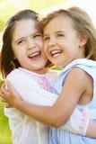 Deux jeunes filles étreignant en zone d'été Image libre de droits