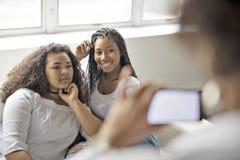 Deux jeunes filles Afro ayant l'amusement ainsi que la mère prenant la photo photos libres de droits