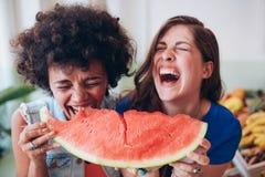 Deux jeunes filles appréciant une pastèque Photos libres de droits