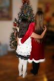 Deux jeunes filles assez habillées par l'arbre de Noël Photos stock