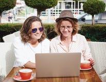 Deux jeunes filles attirantes d'amies de femmes s'asseyent dans un Ca Photos libres de droits