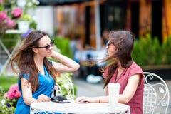 Deux jeunes filles au café d'extérieur Deux femmes après l'achat avec des sacs se reposant en café en plein air avec du café et l Images stock