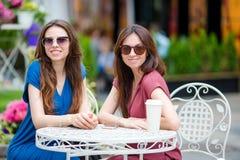 Deux jeunes filles au café d'extérieur Deux femmes après l'achat avec des sacs se reposant en café en plein air avec du café et l Photographie stock libre de droits