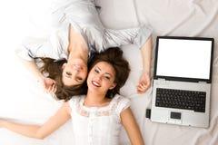 Deux jeunes filles avec l'ordinateur portatif se trouvant sur l'étage Image stock