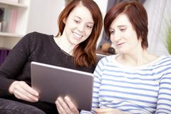 Deux jeunes filles avec la tablette Image stock