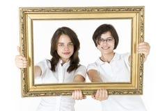 Deux jeunes filles avec le cadre de tableau devant eux Image stock