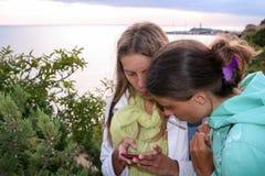 Deux jeunes filles avec le smartphone sur la côte au coucher du soleil pendant l'été Photos libres de droits