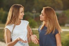 Deux jeunes filles ayant la conversation extérieure Images stock