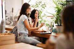 Deux jeunes filles belles avec de longs cheveux foncés, style occasionnel de port, s'asseyent à la table et regardent attentiveme image stock