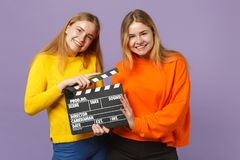 Deux jeunes filles blondes de sourire de soeurs de jumeaux dans des vêtements colorés jugeant la claquette noire classique de cin photographie stock libre de droits