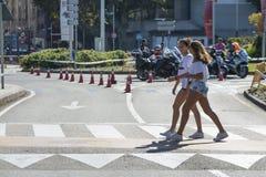 Deux jeunes filles croisent un passage pour pi?tons images stock