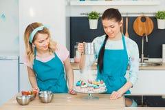 Deux jeunes filles décorant la tasse durcit avec le fruit Photo stock