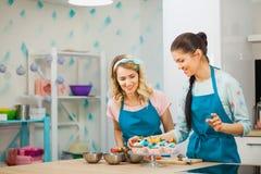 Deux jeunes filles décorant la tasse durcit avec le fruit Image libre de droits