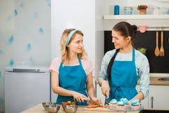 Deux jeunes filles décorant le gâteau de tasse Couper en tranches la fraise Image stock