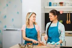 Deux jeunes filles décorant le gâteau de tasse Couper en tranches la fraise Photo libre de droits