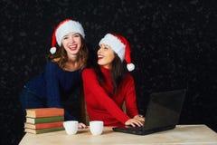 Deux jeunes filles dans des chapeaux rouges Santa de Noël écrivent la lettre à Santa Image libre de droits