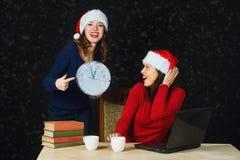 Deux jeunes filles dans des chapeaux rouges Santa de Noël écrivent la lettre à Santa Photos stock