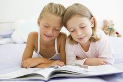 Deux jeunes filles dans des leurs pyjamas, affichant un livre Image stock